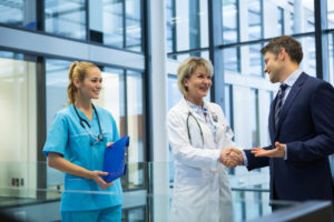 A doctor and healthcare executive shaking hands